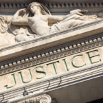 The word Justice on a Courtroom Building. Photo taken in late afternoon directional light.