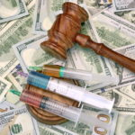 Wood Judges Gavel And Medical Syringe With Injection On The Dollar Cash Background, Overhead View, Concept For Medical Negligence Or Doctor Mistake, Bail, Monetary Compensation